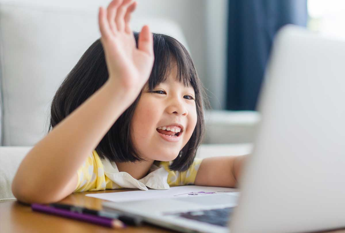 A child raising her hand in front of a laptop screen.