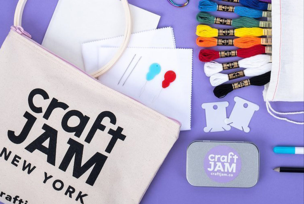 Bag with CraftJam logo and craft supplies on purple table