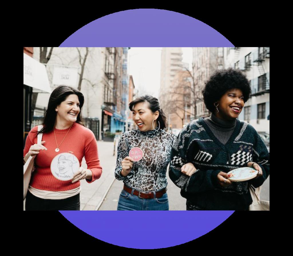 Three women holding crafts walking on city street